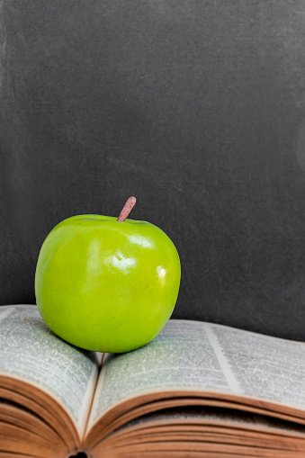 Green Apple On Old Open Book Over Black Chalkboard Background