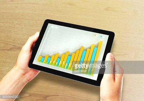 Man holds digital tablet with business chart on a screen
