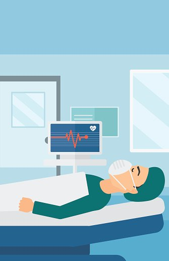 Patient Lying In Hospital Bed With Heart Monitor
