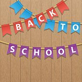 Bunting decoration with Back To School colorful text. Wooden background.