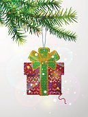 Christmas tree branch with decorative knitted gift