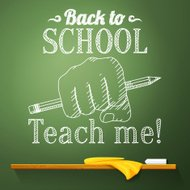 Pencil in the fist on chalkboard with back to school