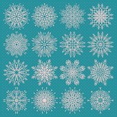 Vector set of sixteen different snowflake silhouettes on blue background.