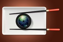 Vector of camera lens on white plate with chopstick.