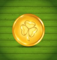 Golden coin with clover on green wooden texture