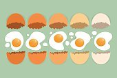 Cracked eggs in different colors on the green background